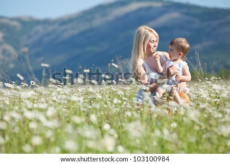 Smiling mother and little baby on nature. Happy people outdoors