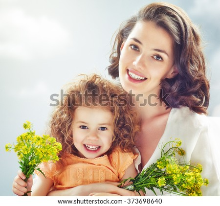 Smiling mother and little child. Happy family outdoors - stock photo