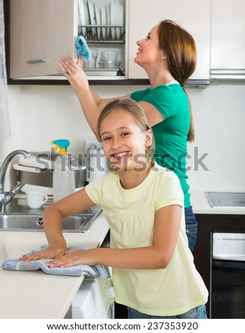 Smiling mother and preschooler daughter cleaning together at home kitchen. Focus on girl  - stock photo