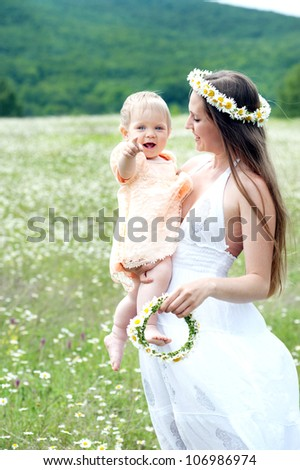 Smiling mother and small child on the environment. Happy people on the street - stock photo
