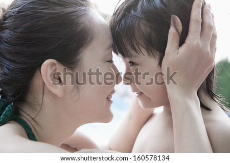 Smiling mother and son embracing and holding head by pool