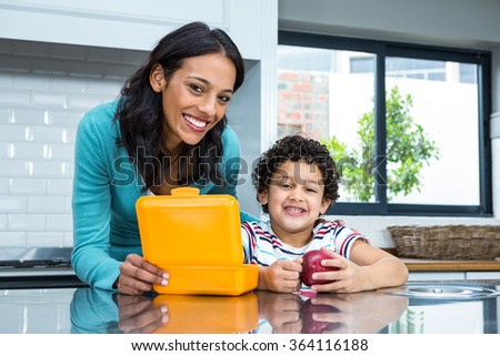 Smiling mother and son going to eat an apple in the kitchen at home