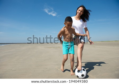 Smiling mother and son playing with ball on the beach - stock photo