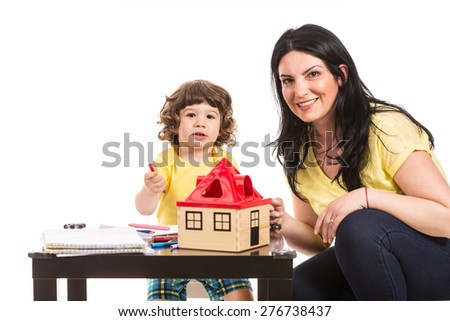 Smiling mother and son sitting at table and doing educational activity together