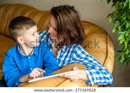 Smiling mother and son using digital tablet, look at a screen with great interest. Technology to stimulate a thriving mind. - stock photo