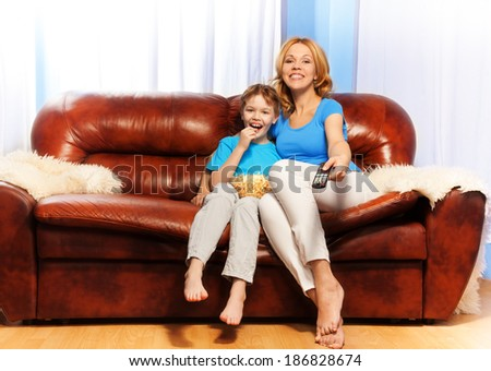 Smiling mother and son watch television at home - stock photo