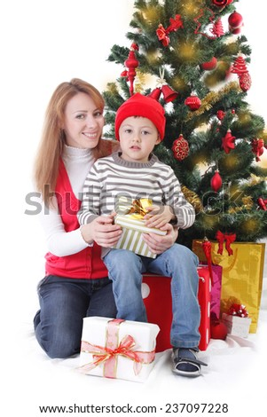 Smiling mother and son with gifts under Christmas tree