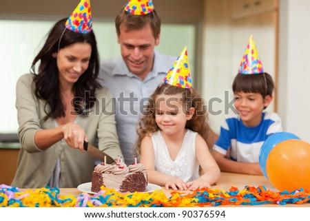 Smiling mother cutting birthday cake - stock photo