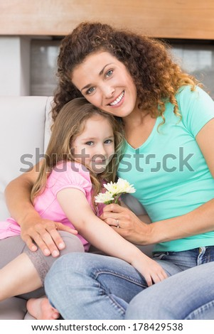 Smiling mother getting little flowers from her cute daughter at home in living room - stock photo