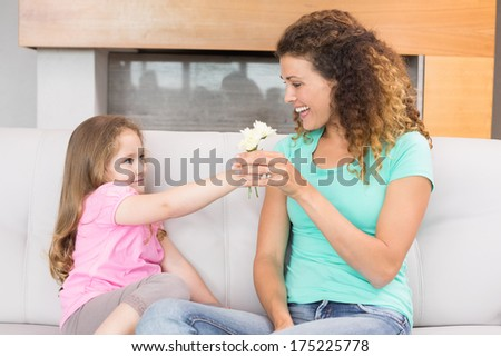 Smiling mother getting little flowers from her daughter at home in living room - stock photo