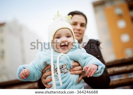 Smiling mother holding her baby boy.Cheerful baby boy having fun with his mother outdoors.Selective focus on baby. - stock photo