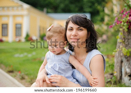 smiling mother holding her baby on lap - stock photo