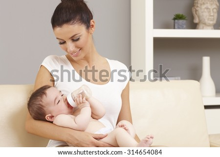 Smiling mother holding naked little baby in arms. Baby drinking from feeding bottle.
