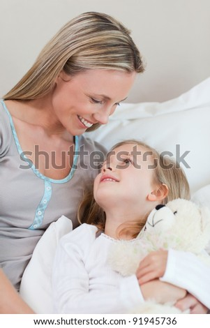 Smiling mother hugging her daughter on the bed