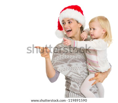 Smiling mother in Christmas hat and baby girl pointing on copy space