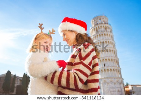Smiling mother in Christmas hat and cosy sweater and daughter wearing funny reindeer antlers standing in front of Leaning Tour of Pisa, Italy. They spending exciting Christmas time traveling. - stock photo