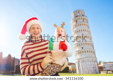 Smiling mother in Christmas hat and daughter wearing funny reindeer antlers showing Italian flag in front of Leaning Tour of Pisa, Italy. They spending exciting Christmas time traveling. - stock photo