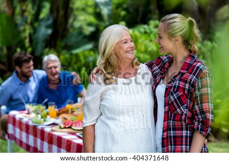 Smiling mother-in-law and daughter-in-law standing at yard - stock photo