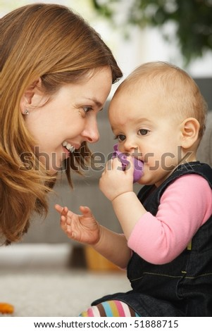 Smiling mother leaning close to baby girl in closeup. - stock photo