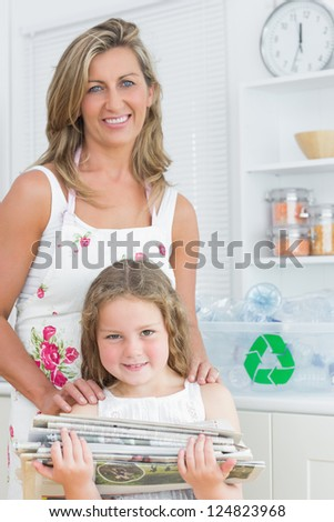 Smiling mother standing behind her daughter who is holding old newspaper - stock photo