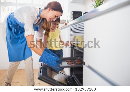 Smiling mother taking cookies out of the oven in the kitchen - stock photo