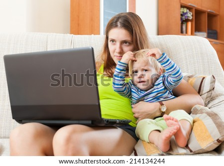 Smiling mother with baby working  with computer at home - stock photo