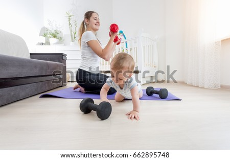 Smiling mother with her baby boy exercising on floor with dumbbells