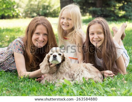 smiling mother with her daughters and dog on a grass - stock photo