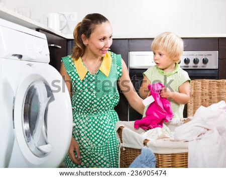 Smiling mother with little daughter loading clothes into washing machine in home  - stock photo