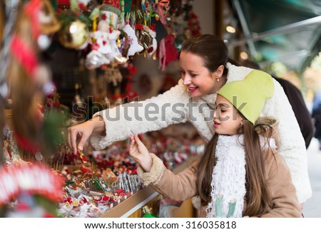Smiling mother with positive girl in Christmas market. Focus on girl - stock photo