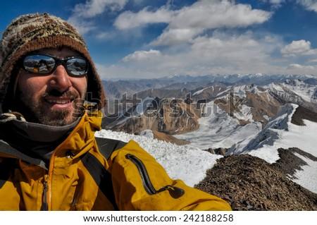 Smiling mountaineer on mountain summit in Pamir mountains in Tajikistan - stock photo