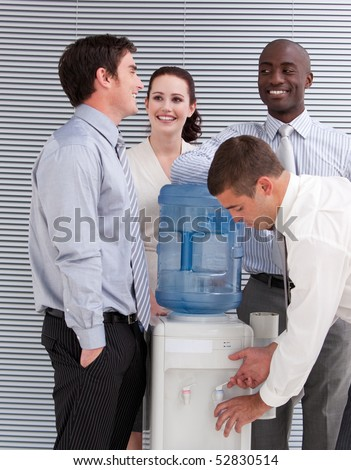 Smiling multi-ethnic business people interacting at a watercooler in the office - stock photo