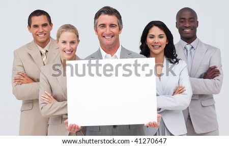 Smiling multi-ethnic business team holding a white card - stock photo