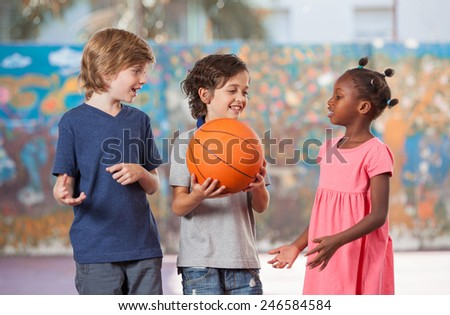 Smiling multi ethnic kids playing in schoolyard. - stock photo