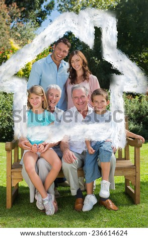 Smiling multi generation family sitting on bench in park against house outline in clouds - stock photo