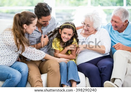 Smiling multi-generation family sitting on sofa at home - stock photo