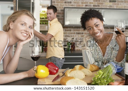 Smiling multiethnic women holding wine glasses at kitchen counter with man in background - stock photo