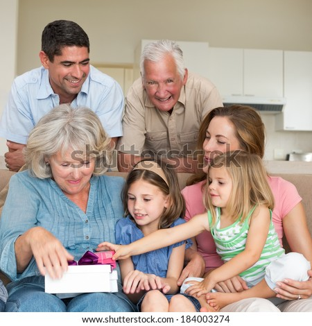 Smiling multigeneration family with gifts in sitting room - stock photo