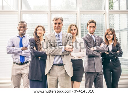 Smiling multiracial business team standing and looking confident at camera - Group of business people in the office, concepts about teamwork and business - stock photo