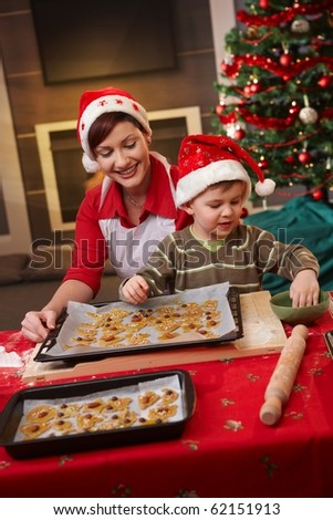 Smiling mum and small son decorating christmas cake together at table.?