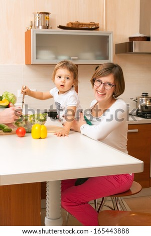 smiling mum with the kid in the kitchen - stock photo