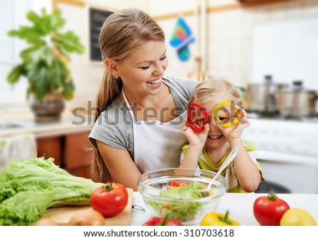 Smiling mummy and her cute daughter having fun cooking vegetarian dinner. Little child playing with colorful pepper rings while preparing salad with mother.  - stock photo