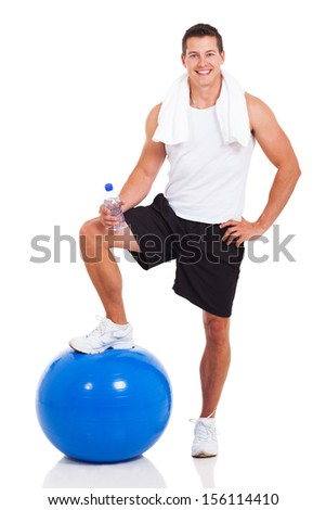 smiling muscular man with water bottle and fitness ball on white background