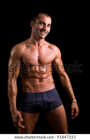 Smiling muscular young man posing against black background - stock photo