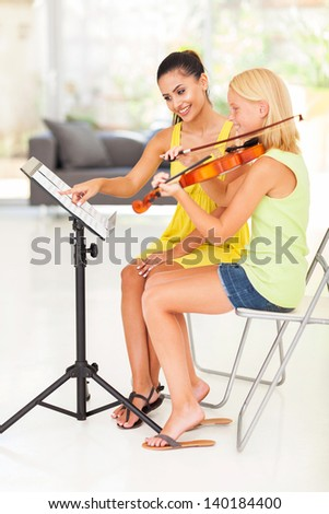 smiling music teacher pointing notes for violin student - stock photo