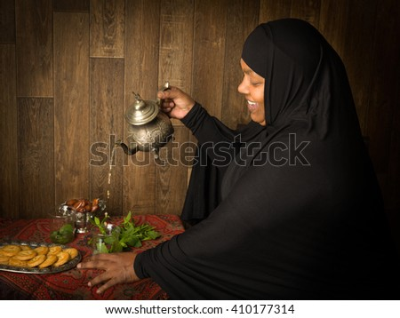 Smiling muslim woman pouring mint tea the traditional way - stock photo