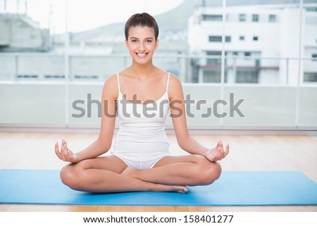 Smiling natural brown haired woman in white sportswear practicing yoga in bright living room