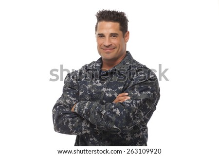 Smiling navy man posing with arms crossed against white background - stock photo