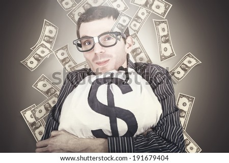 Smiling nerd businessman holding a bag full of money beneath falling US dollar notes in a depiction of smart financial gains - stock photo