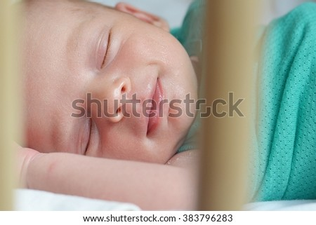 Smiling newborn baby sleeping in a cot